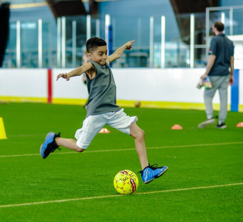 A young boy kicks a soccer ball on the turf field at Warinanco Park